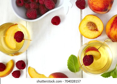 Peach wine and fruits on white wooden table, top view, copy space, frame