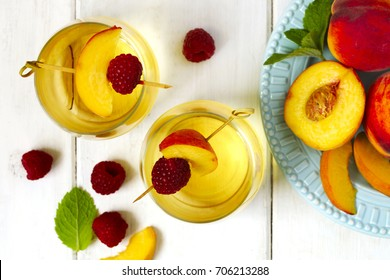 Peach wine and fruits on white wooden table, top view