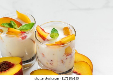 peach yogurt with mint in glasses with fresh fruits on white marble table. healthy breakfast. close up with copy space