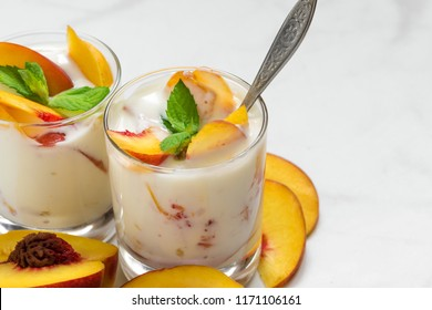 peach yogurt with mint and spoon in glasses with fresh fruits on white marble table. healthy breakfast. close up with copy space