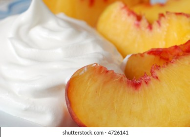 Peaches and Cream.  Closeup of freshly sliced peaches with whipped topping on light blue plate.  Shallow dof