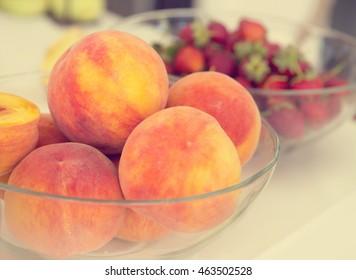 Peaches in a glass dish.