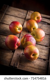 Peaches group slanted on old rustic wooden box and dark background in studio