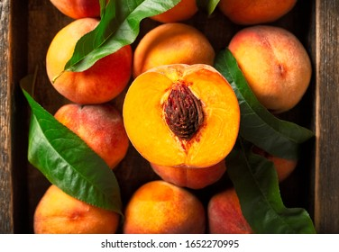 Peaches with leaves in a wooden box with peach in halves on top. Flat lay composition with ripe juicy peaches. Harvest of peaches for food or juice. Top view fresh organic fruit, vegan food.