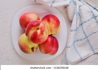Peaches and nectarines on a plate. Nectarines on a white background.Ripe juicy nectarines. Focus Selective.