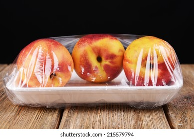 Peaches packed in food film on table on black background