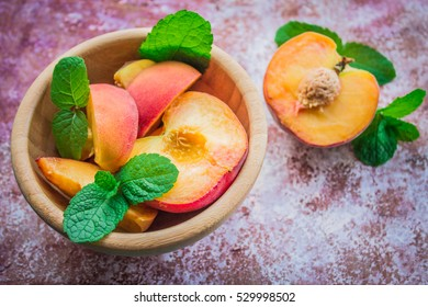 Peaches in a plate on a wooden background.