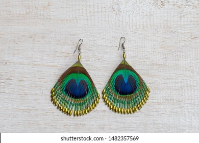 Peacock feather earrings on white wooden background, close up. Earrings made of peacock feathers. Top view