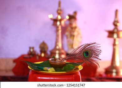 Peacock feather, known as Mayilpeeli in Malayalam, is dipped in a bowl of henna paste which is used to dye Indian brides' palm before wedding on the background of traditional Kerala brass lamp
