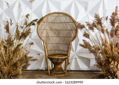 Peacock wicker chair in a spacious bedroom interior. Rattan peacock armchair by the white empty wall in the living room. Scandinavian style home. Rustic room interior. Eco furniture, natural furniture