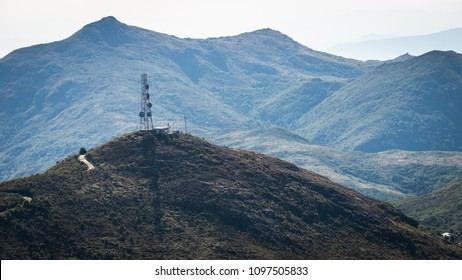 A peak with an antenna tower surrounded by higher mountains