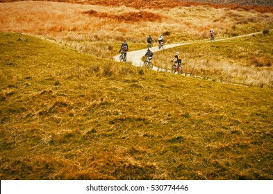 Peak District National Park, England, Europe. Group of riders cyclists riding uphill one behind other during  race.