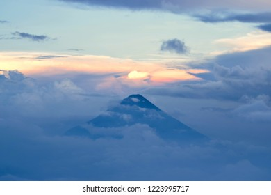 """Peak of the Guatemalan """"Vulcano de Agua"""" at dusk while sun is setting and reddening the clouds, as seen from the top of the Acatenango Volcano, at the height of 3700m"""