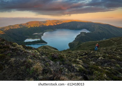 the peak of Lagoa do Fogo in the Azores at sunset with father and son enjoying the view