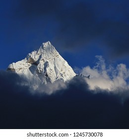 Peak of Mount Ama Dablam surrounded by dark clouds, Everest National Park, Nepal.
