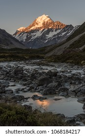 The peak of Mount Cook lit up by the last of the sunlight at sunset, reflected in the Hooker River. From the Hooker Valley Track, Aoraki/Mount Cook National Park New Zealand.
