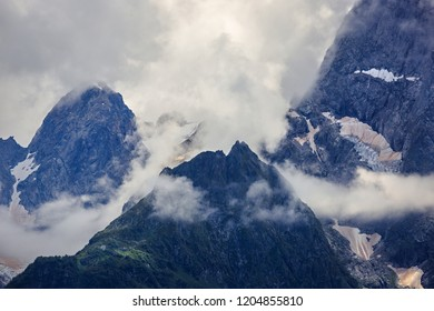 Peak of the mountain with glaciers against the background of clouds and sky. Caucasian ridge, Russia.