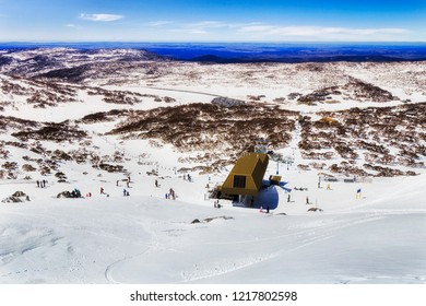 From the peak of Mt Back Perisher high in Snowy Mountains of Australia looking down to chairlift station for snowboarders and skiers above Perisher valley snow fields and ski resort slopes.