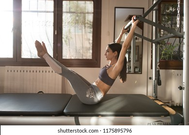 Peak Pilates - Young Woman Exercising on Peak Pilates Reformer, Pilates Instructor - Editorial