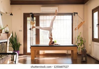 Peak Pilates - Young Woman Exercising on Peak Pilates Reformer, Pilates Instructor - Editorial