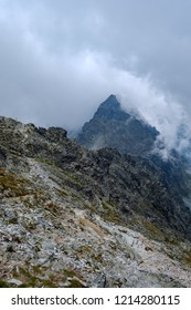 peak of Rysy mountain covered in mist. autumn ascent on rocky hiking trails. Border of Slovakia and Poland
