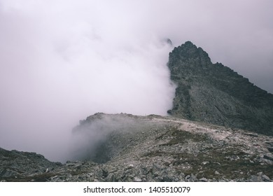 peak of Rysy mountain covered in mist. autumn ascent on rocky hiking trails. Border of Slovakia and Poland - vintage old film look