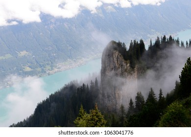 A peak with trees and a rockface in the cloudy and the lake Brienzersee in the background