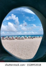 A peak view through a hole looking our on the beach in Cancun, Mexico.  A colorful parasail can be seen floating over the blue ocean.