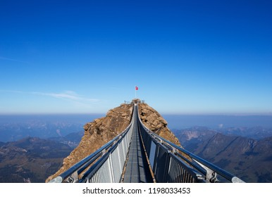 Peak walk on the Glacier 3000 in the canton of Vaude in Switzerland. Top of the mountain in the alps. Suspension bridge on the summit in the alpine area. Swiss flag in the middle of a peak.