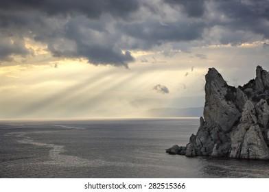 Peaked rock in sea with dramatic sky. Crimea, Novy Svet, Karaul-Oba.