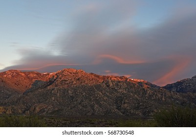 Peaks of Catalina mountains in Tucson, Arizona, USA, in evening sunshine glow with dramatic cloud