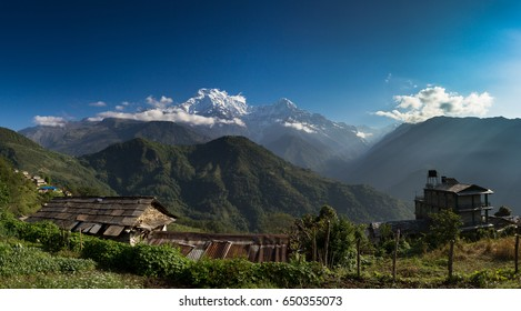 Peaks of the Himalayas brushed by cloud rise into the turquoise blue morning sky. A mountain village nestles on a hillside in the foreground.