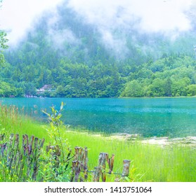 The peaks and lakes of jiuzhaigou, China -- summer 2017: peaks within the jiuzhaigou scenic area, amid clouds and clouds.The plants in the fence, the blue lake.