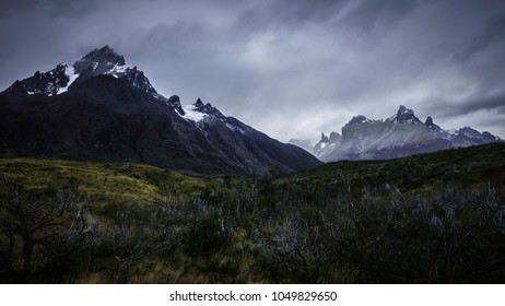 The peaks of the Torres del Paine in Patagonia Chile can be seen. On the right is the 'Paine Grande'. Below, you can see many wild vegetation of a reddish tone due to autumn season