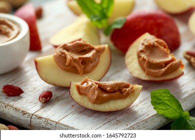 Peanut butter and apple to snack. on white wooden board