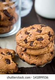 Peanut butter chocolate chip cookies with milk on a wooden table.