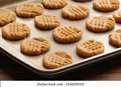 Peanut butter cookie dough on baking sheet in natural kitchen light.