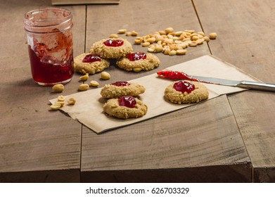 Peanut butter cookies with strawberry jam on wooden table