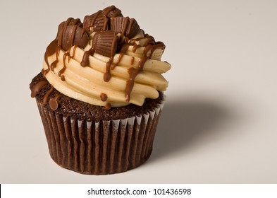 A Peanut Butter Cupcake Drizzled with Chocolate Syrup on White