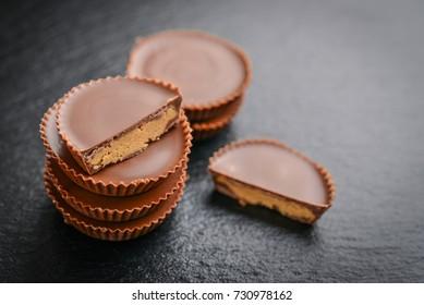 Peanut butter cups, chocolate dessert on black background  closeup
