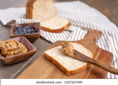 Peanut Butter, Grape Jelly, Bread, Gathered to Make Peanut Butter and Jelly Sandwiches on a Wooden Table