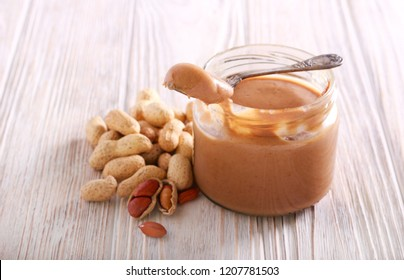 Peanut butter in a jar on wooden table