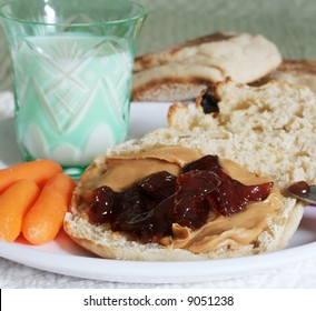 peanut butter and jelly on toasted muffin with carrots and milk