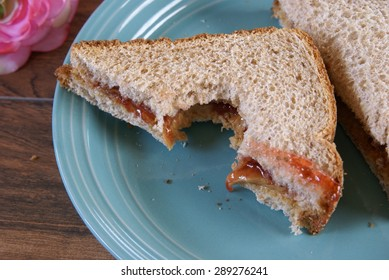 Peanut butter and jelly sandwich half with a bite taken out of it.