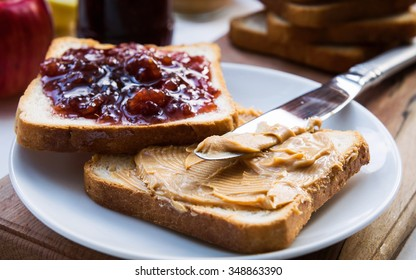 Peanut butter and raspberry jelly sandwich on wooden background. Perfect sweet breakfast. Close up.