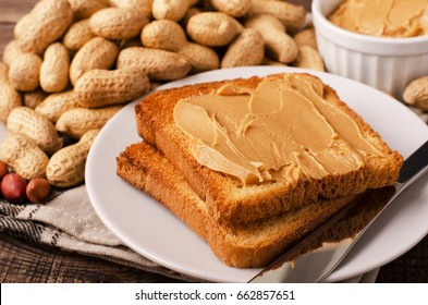 Peanut butter sandwich on plate with inshell peanuts, breakfast on the wooden background