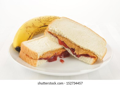 A peanut butter sandwich with strawberry jam and a banana
