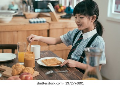 Peanut butter sandwich toast bread on wooden table kitchen at home morning. smiling happy little kid elementary school student in uniform before study eating breakfast. cute child having healthy meal