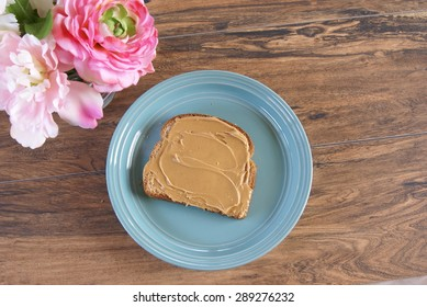 Peanut butter spread on a slice of whole wheat bread and laying on a green plate.