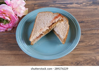 Peanut butter and strawberry jam on wheat bread, cut in half to form half sandwich triangles.
